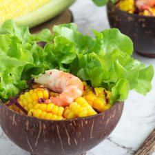 dairy free thai corn salad with prawn in a coconut shell bowl