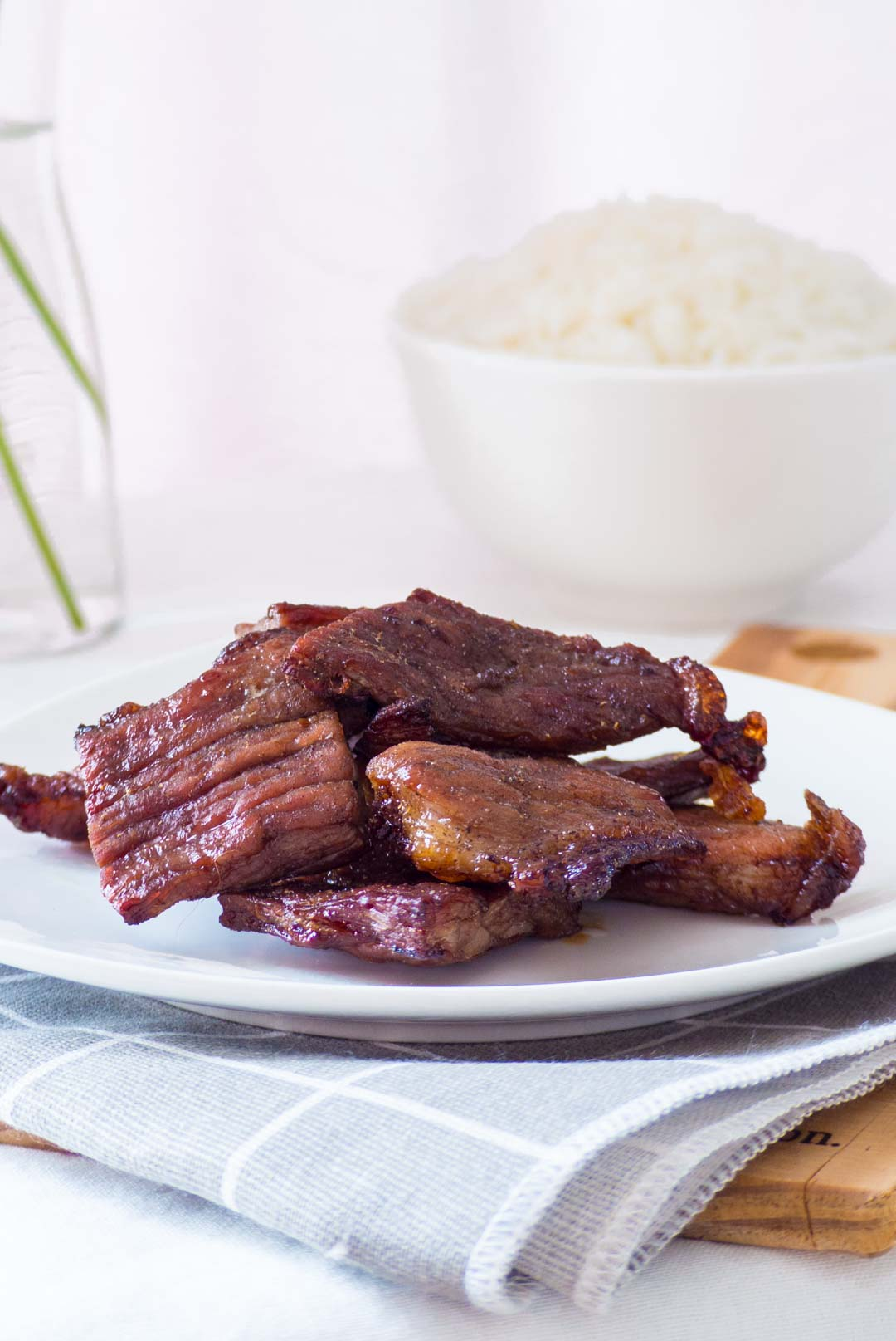 thai fried sun-dried beef on a white plate with a bowl of rice in the background