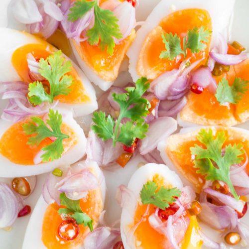 thai medium boiled egg salad on a white plate