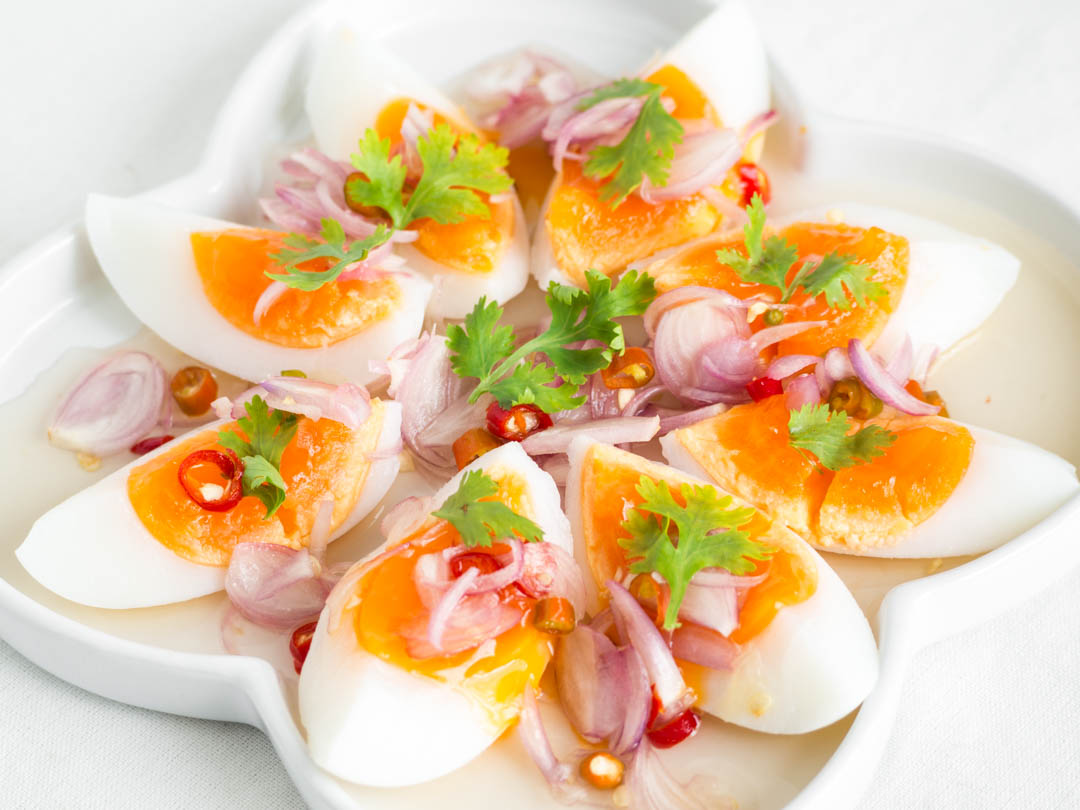 thai medium boiled egg salad on a white plate
