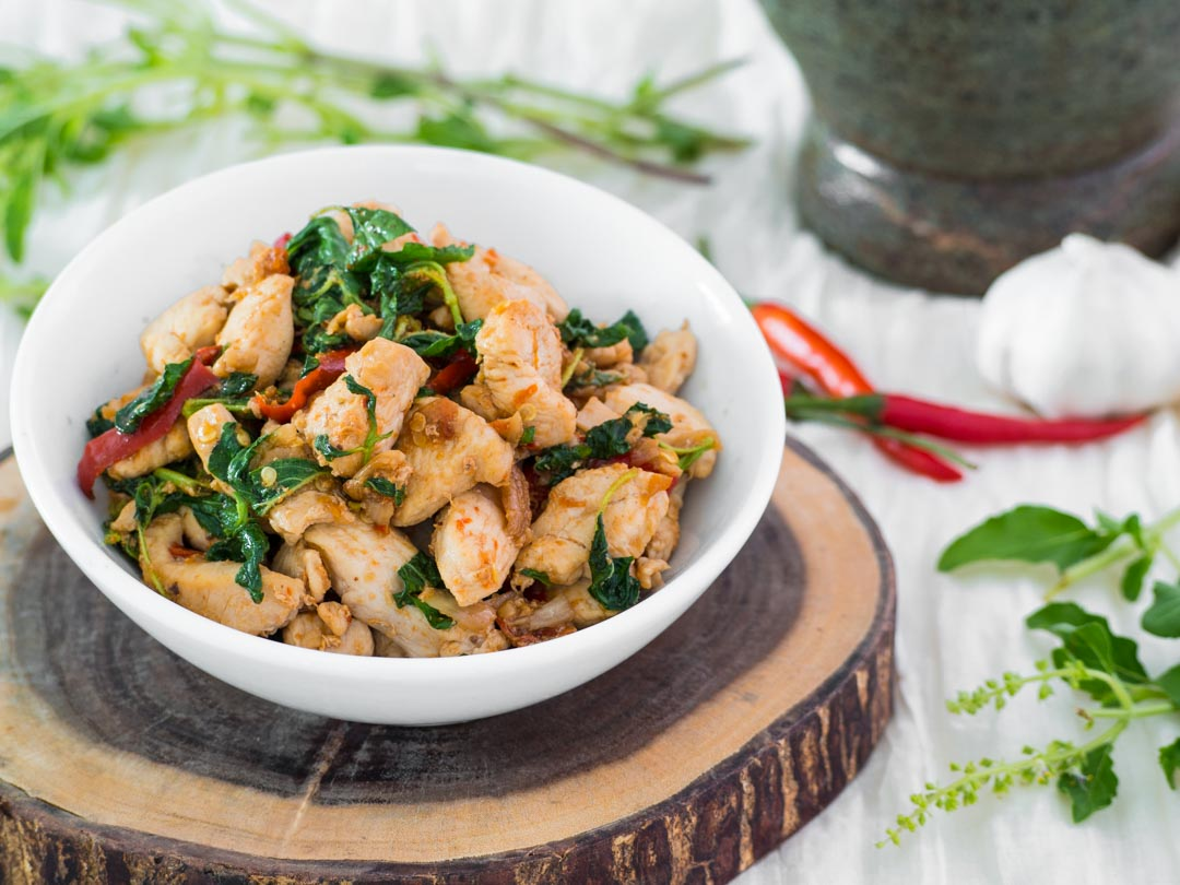 thai holy basil chicken or pad kraprao gai in a white bowl