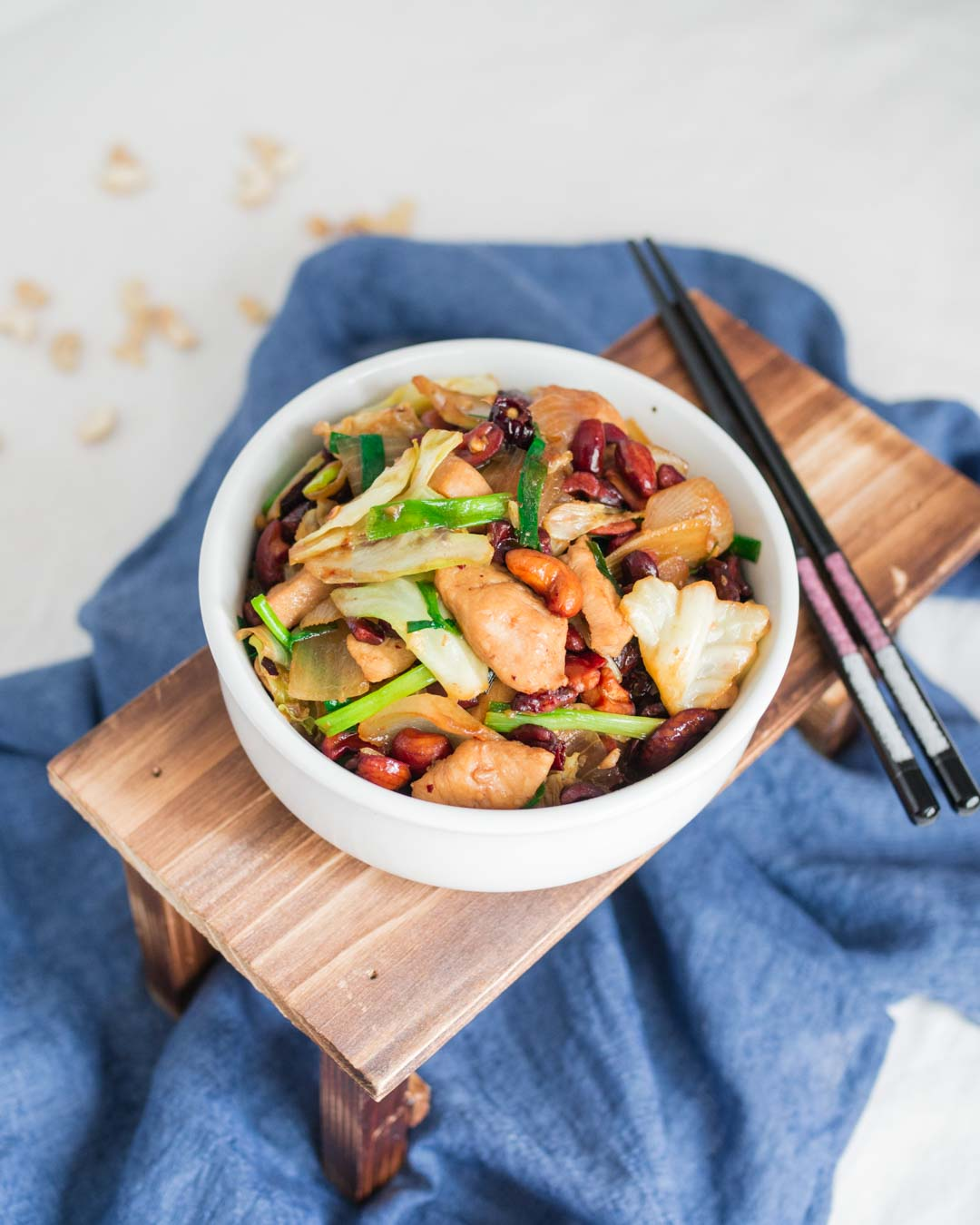 Thai cashew chicken in a white bowl with a pair of chopsticks