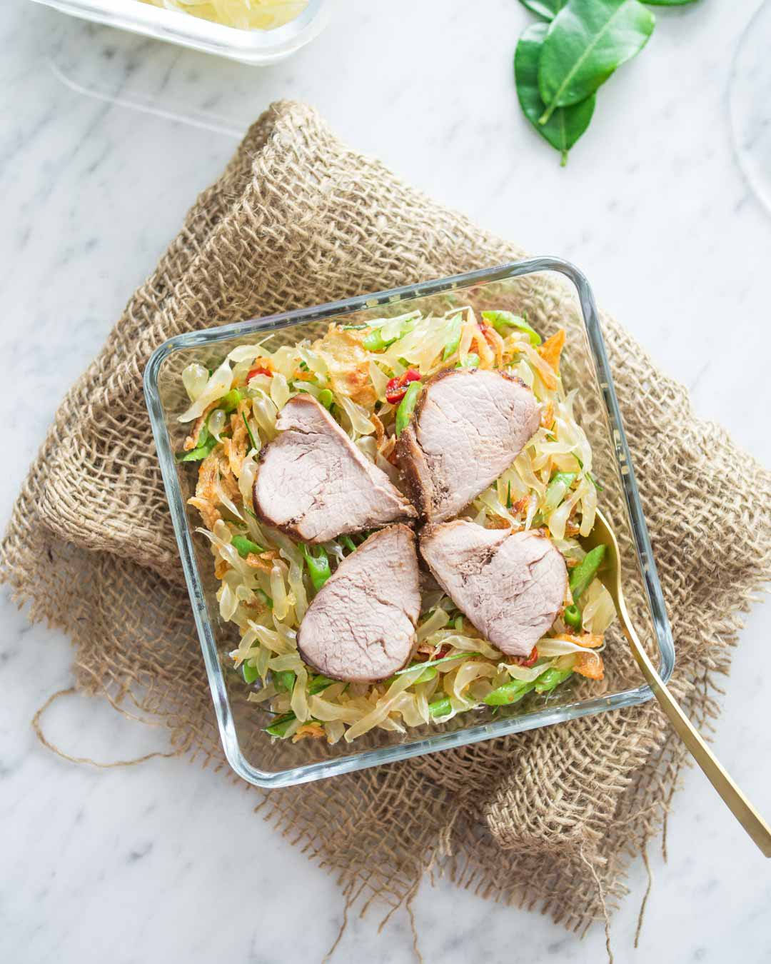 Thai pomelo salad with grilled pork in a glass bowl