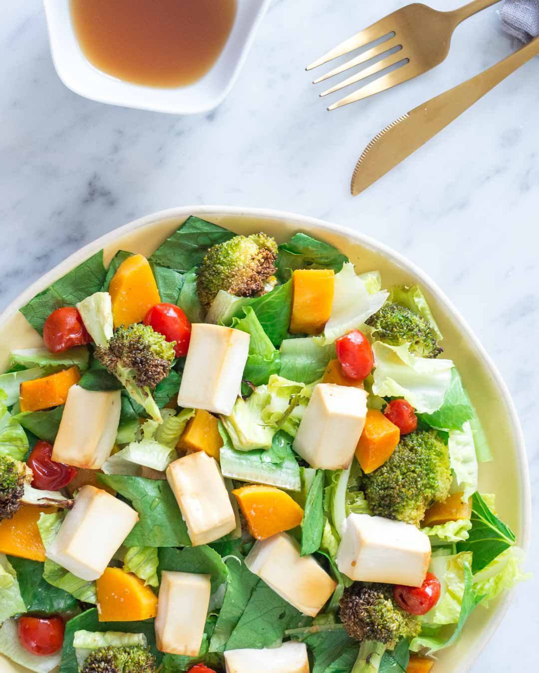 tofu salad on a plate with a bowl of salad dressing and a fork and a knife