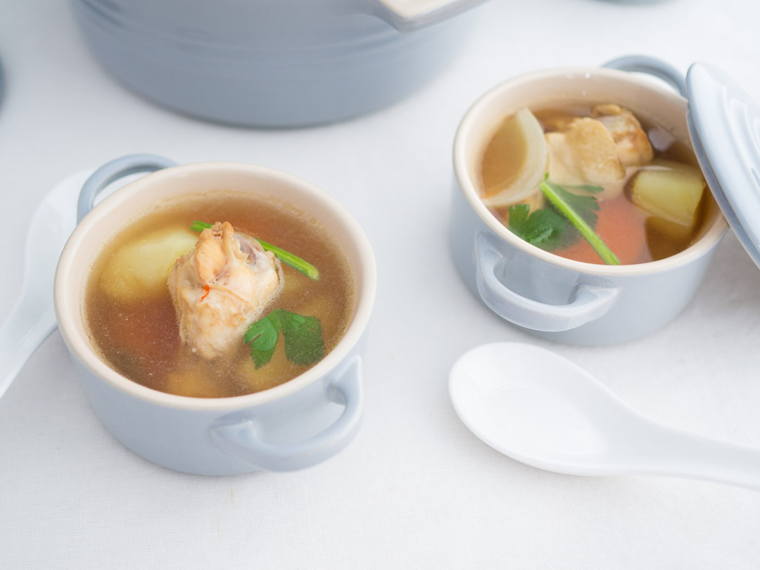 two bowls of Thai potato soup with chicken drumettes