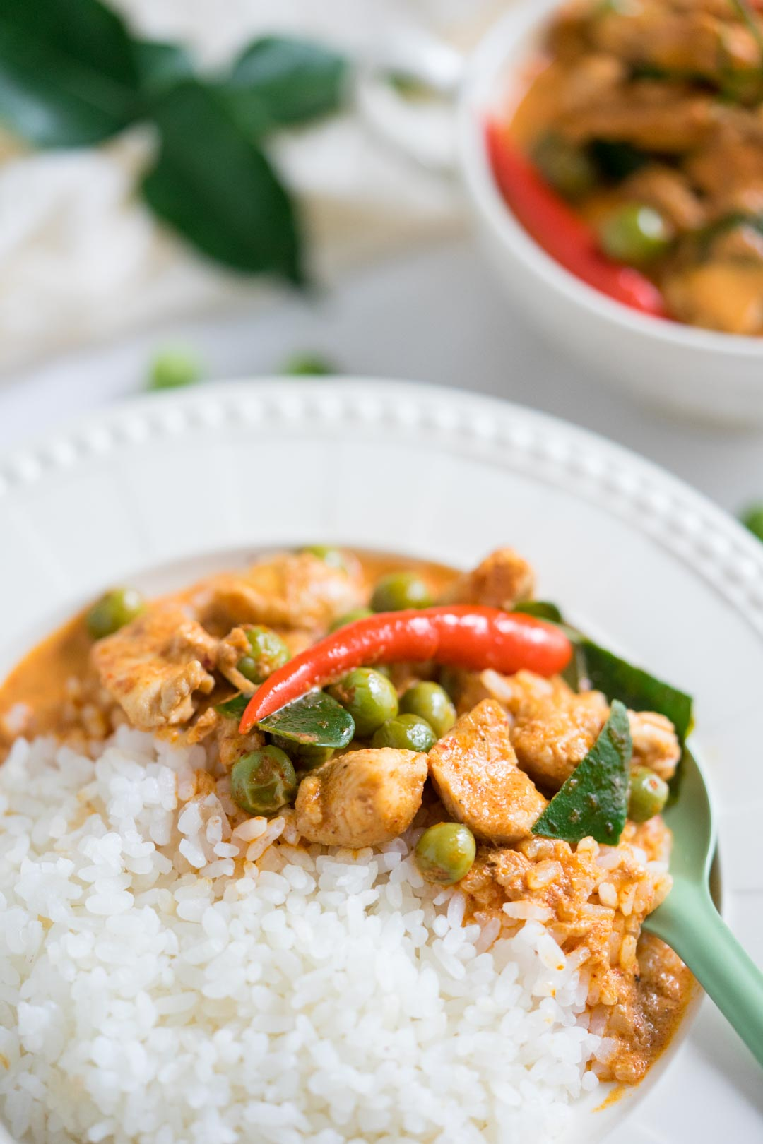 rice topped with panang chicken or panang gai in a white plate