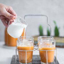 milk being poured into a glass filled with ice and Thai tea