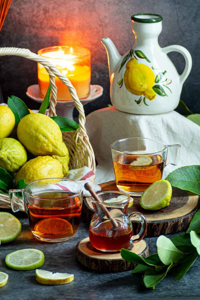 two cups of honey and lemon tea with a jar of honey and lemons in a basket