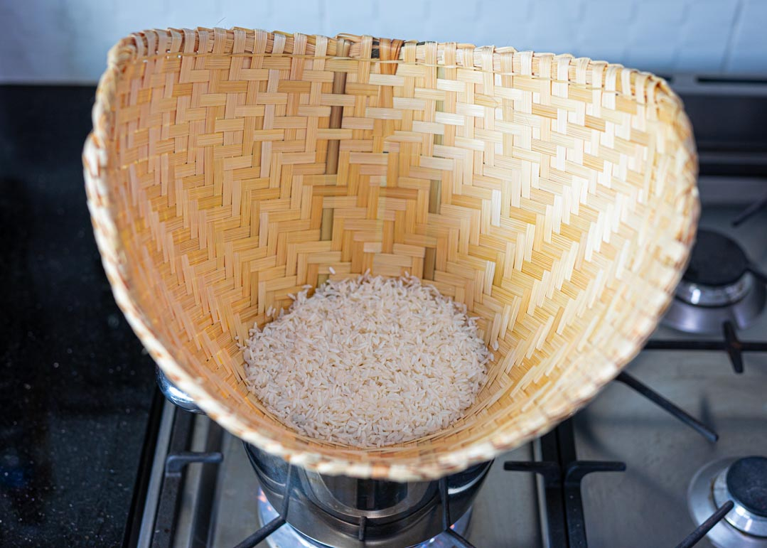 raw Thai sticky rice in a bamboo steamer basket on a stove