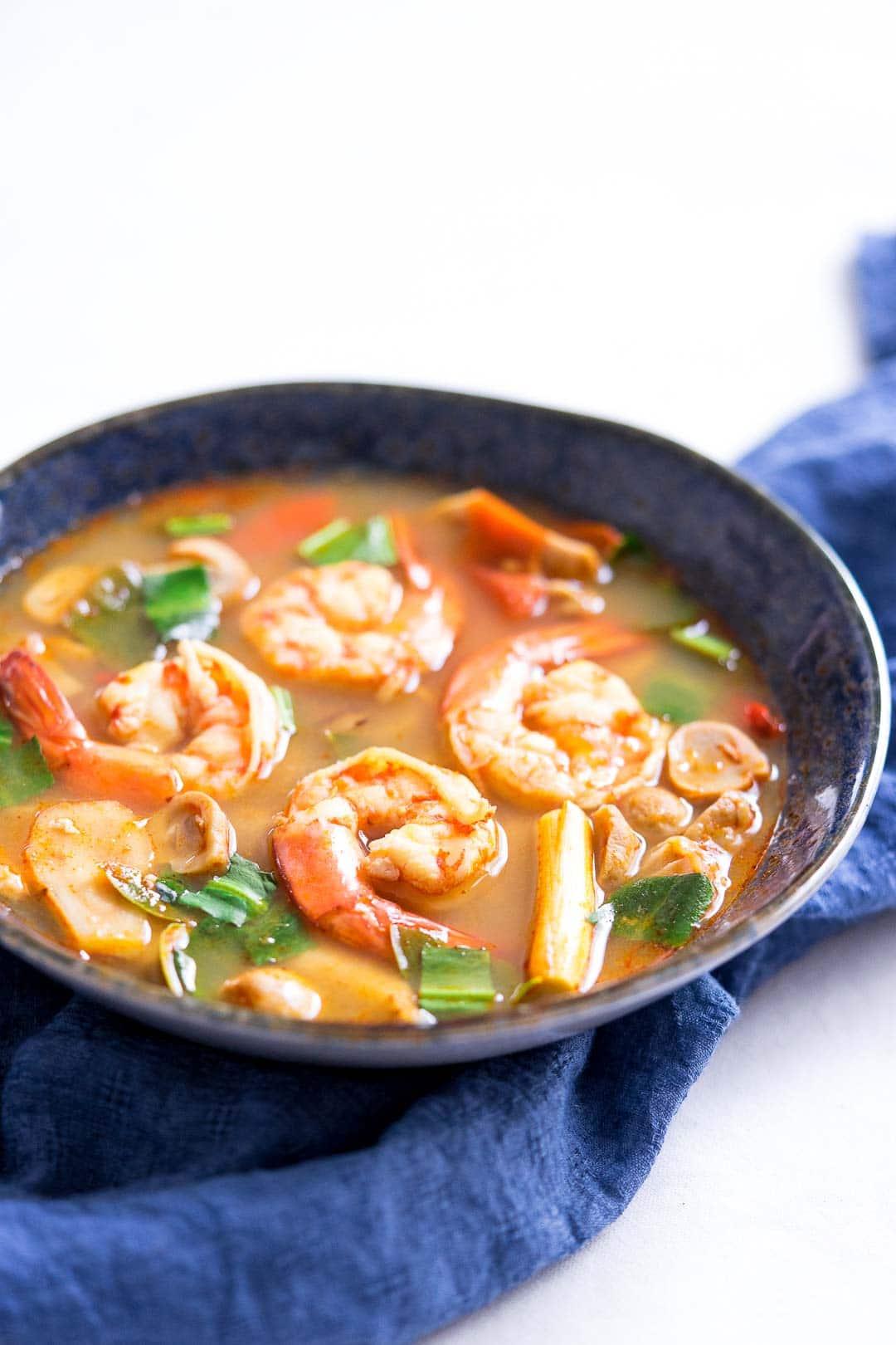 tom yum gung or Thai lemongrass soup with prawn in a blue bowl