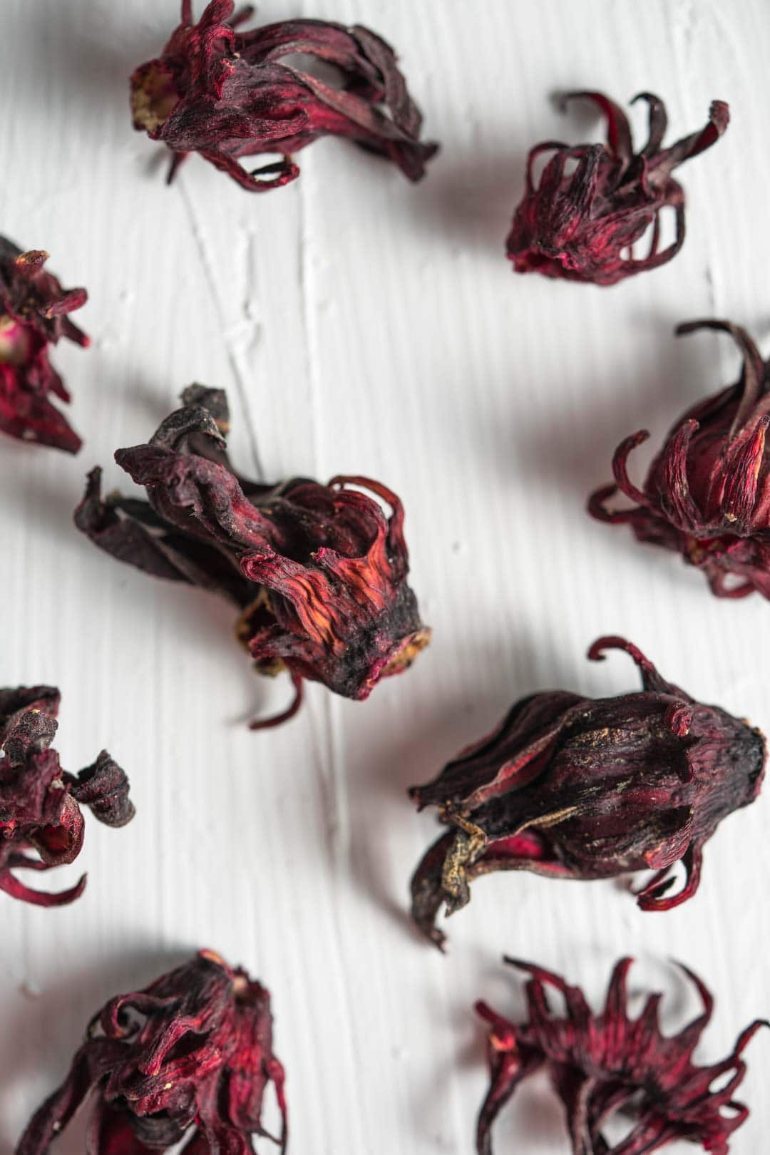 dried roselle flowers scattered around a white table