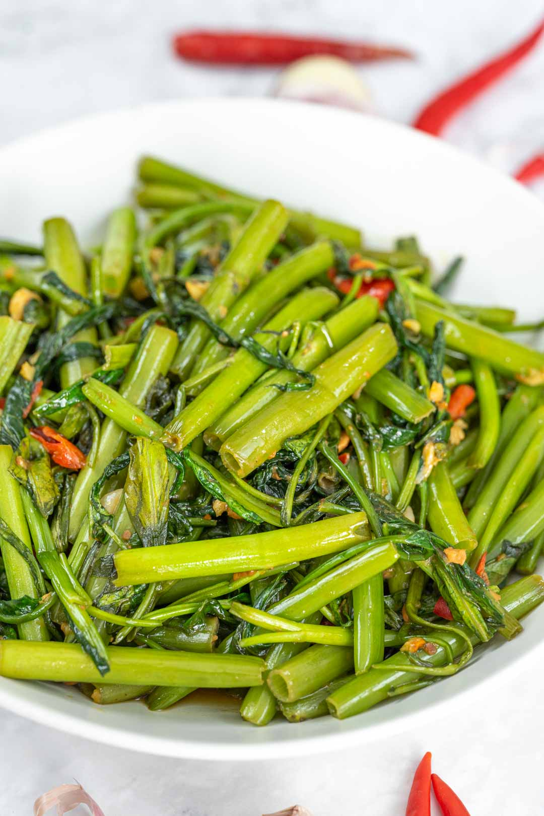 stir-fried water spinach in a white plate