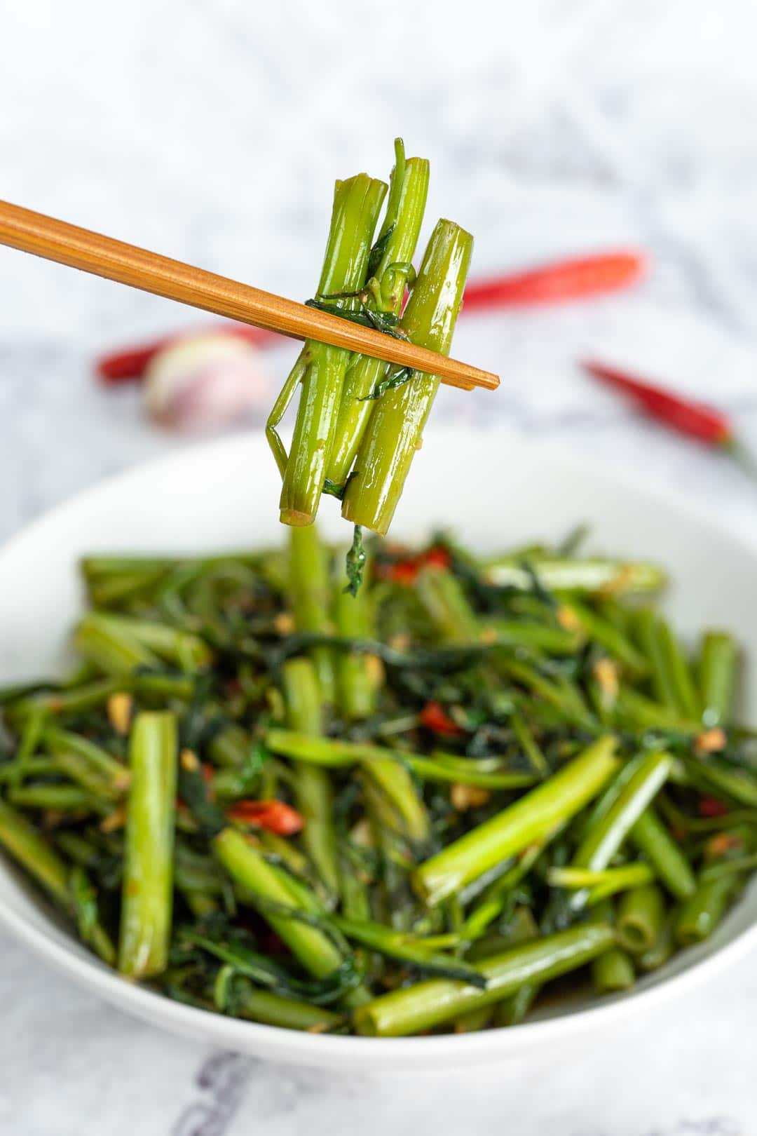 stir-fried morning glory lifted up from plate with a pair of chopsticks