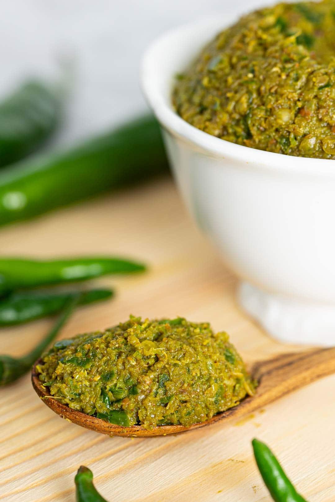 prik gaeng keow wan (พริกแกงเขียวหวาน) or Thai green curry paste in a wooden spoon
