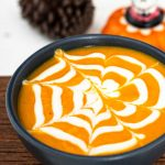 a cup of spooky Halloween soup with a spiderweb