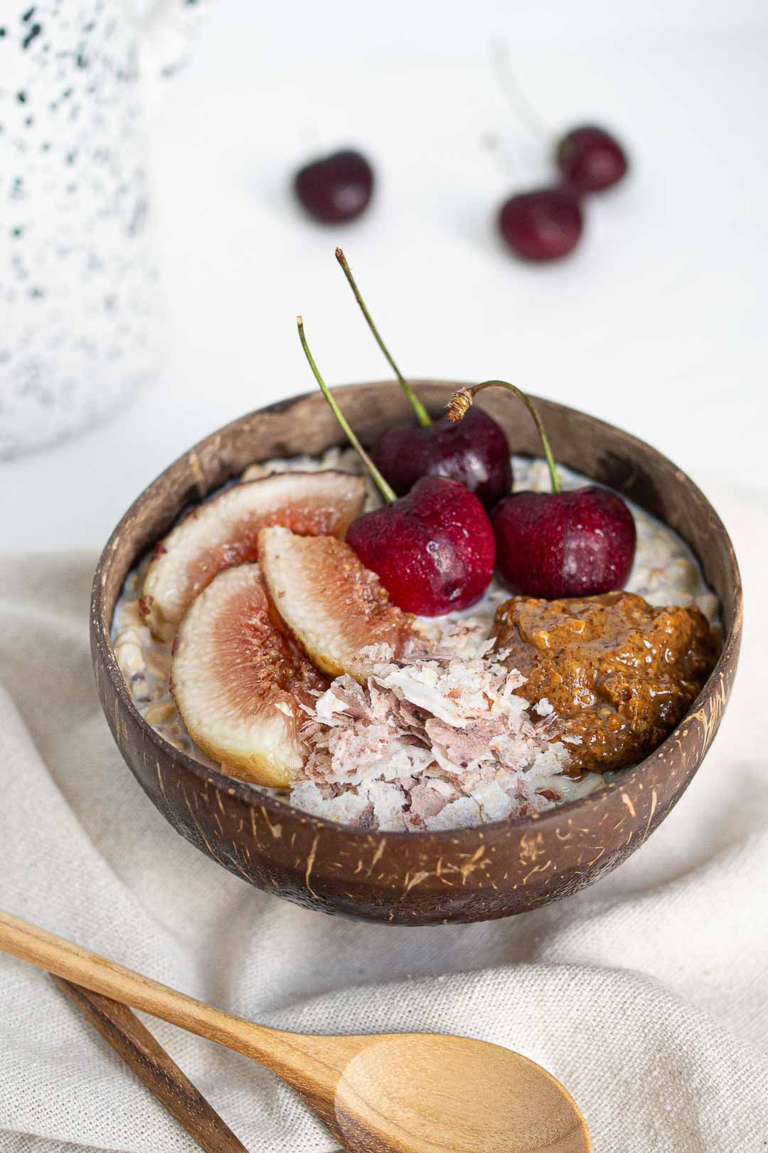 almond milk overnight oats with fig, brown rice flakes, cherries and almond butter in a coconut bowl