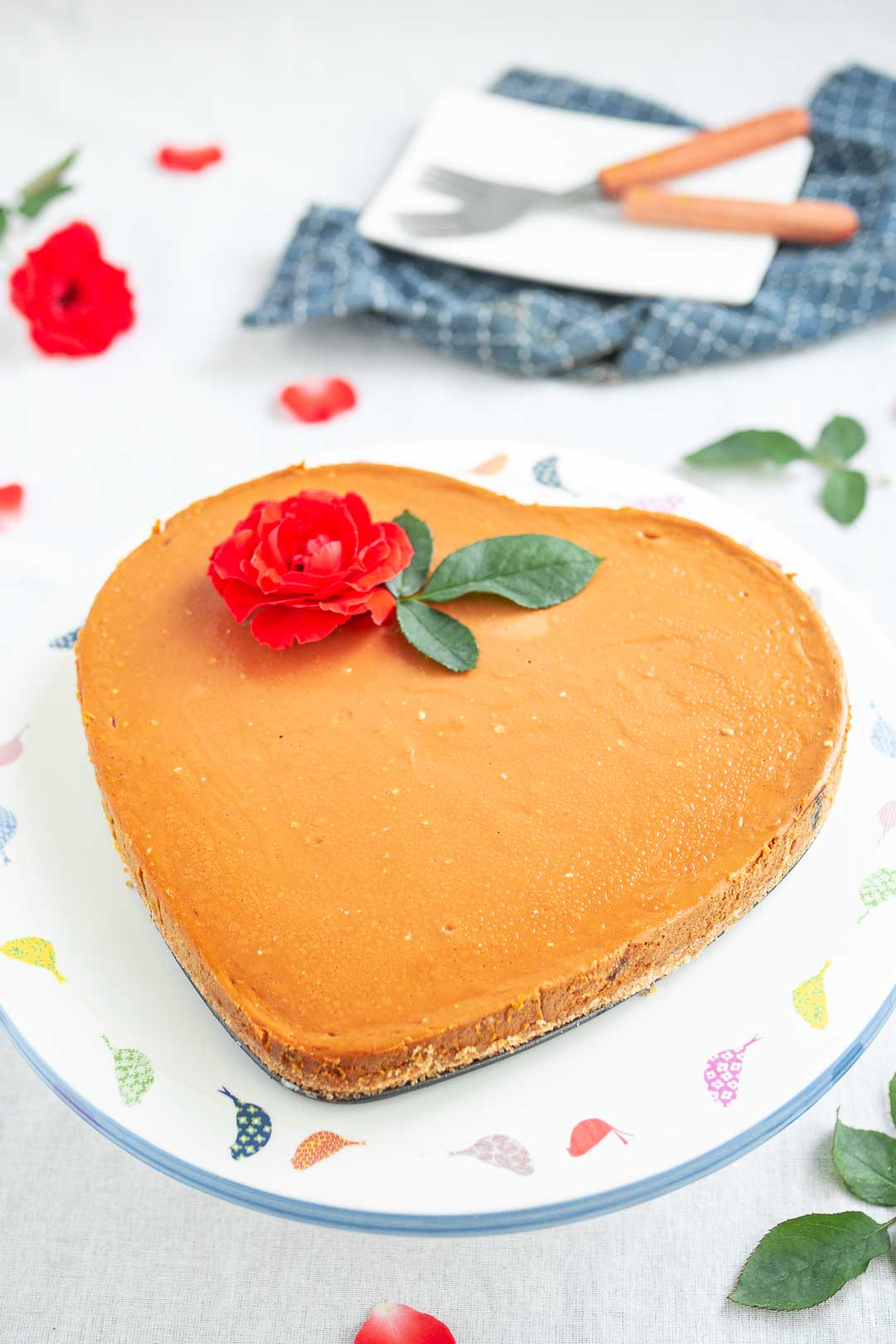 a heart-shaped cake garnished with a red rose that's perfect for Valentine's Day