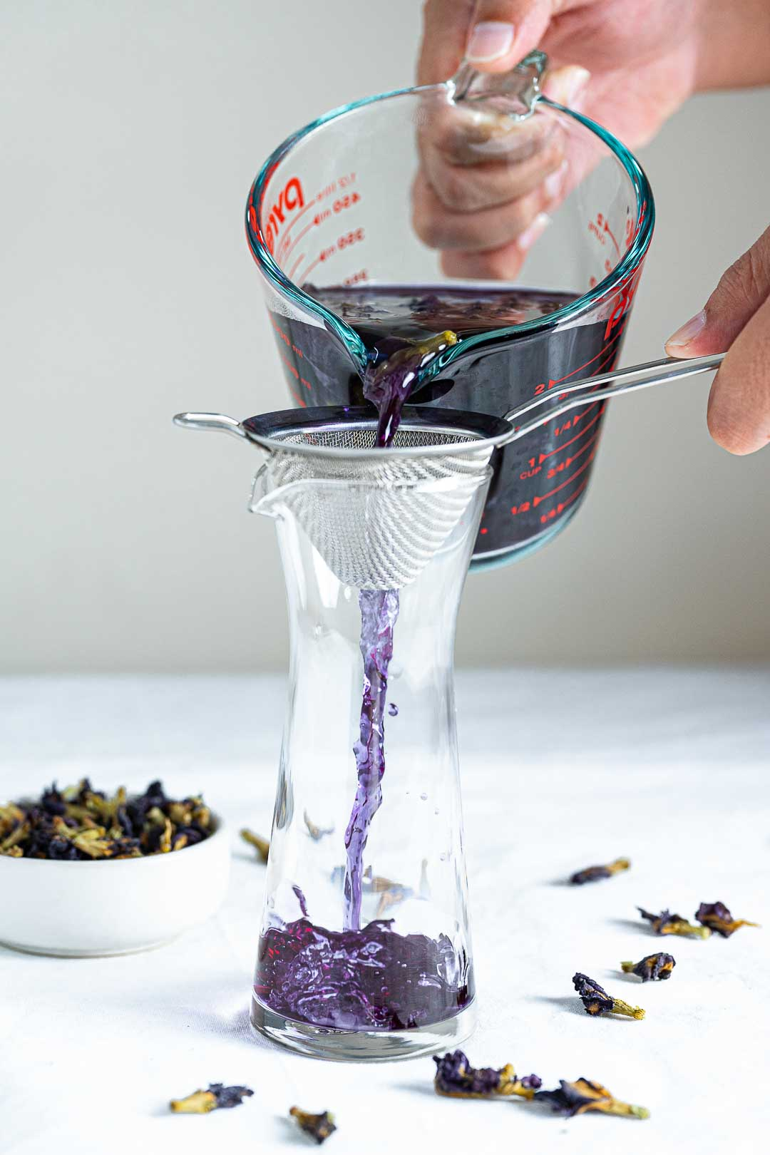 Blue Tea Being Poured Into A Pitcher