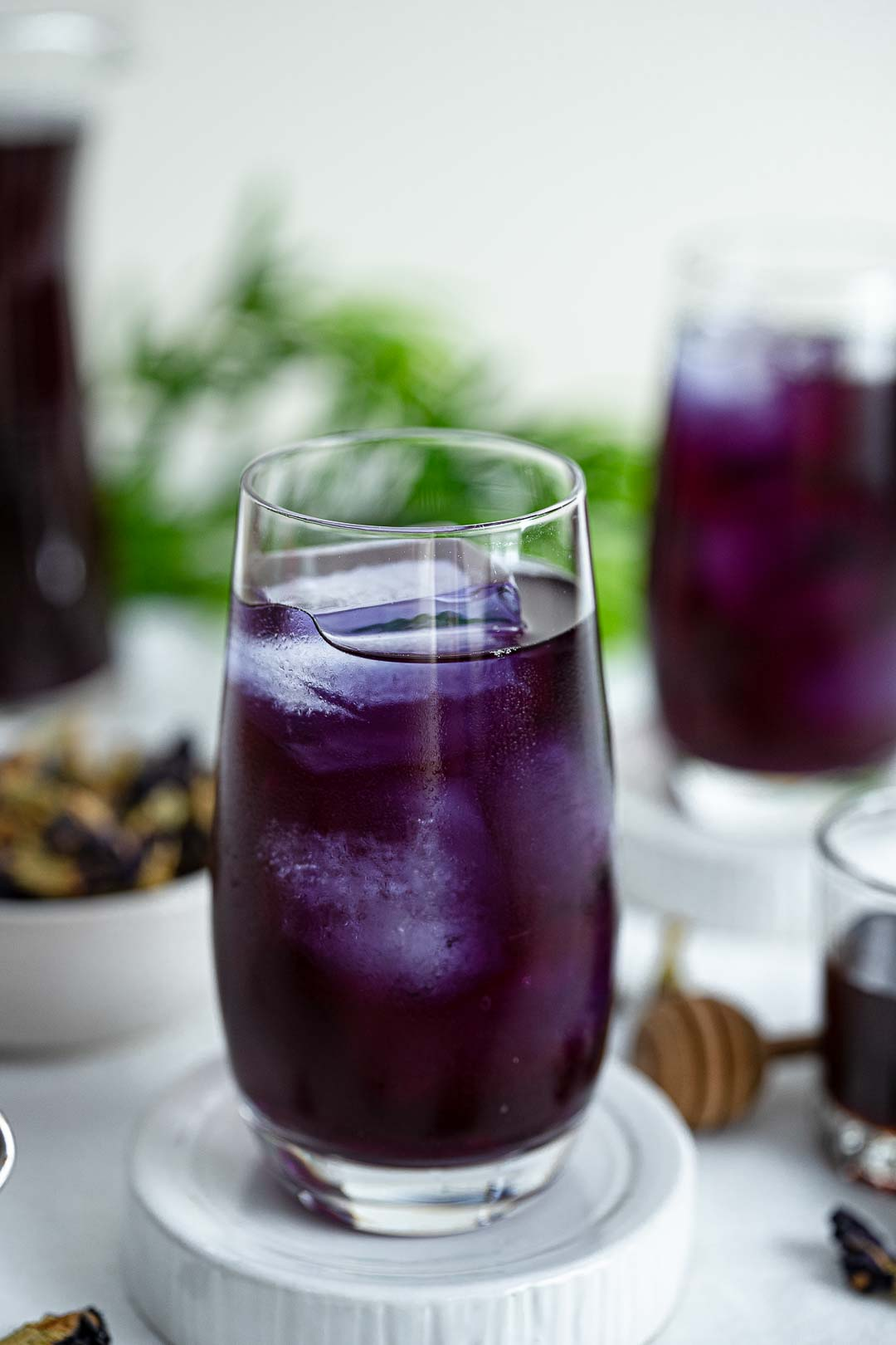 A Glass Of Butterfly Pea Tea With Ice In It