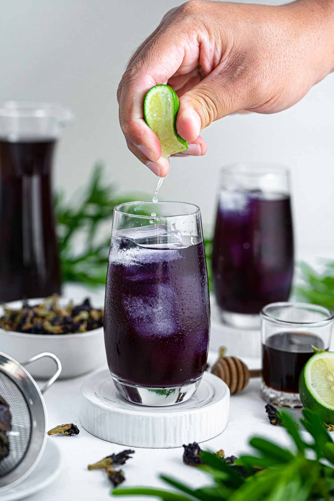 Lime Being Squeezed Into A Glass Of Butterfly Pea Tea Or Blue Tea