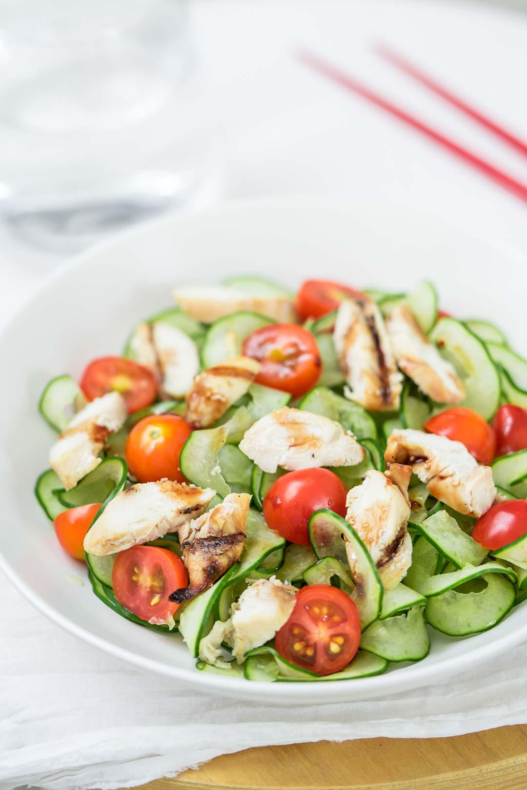 chicken tomato cucumber salad in a white dish