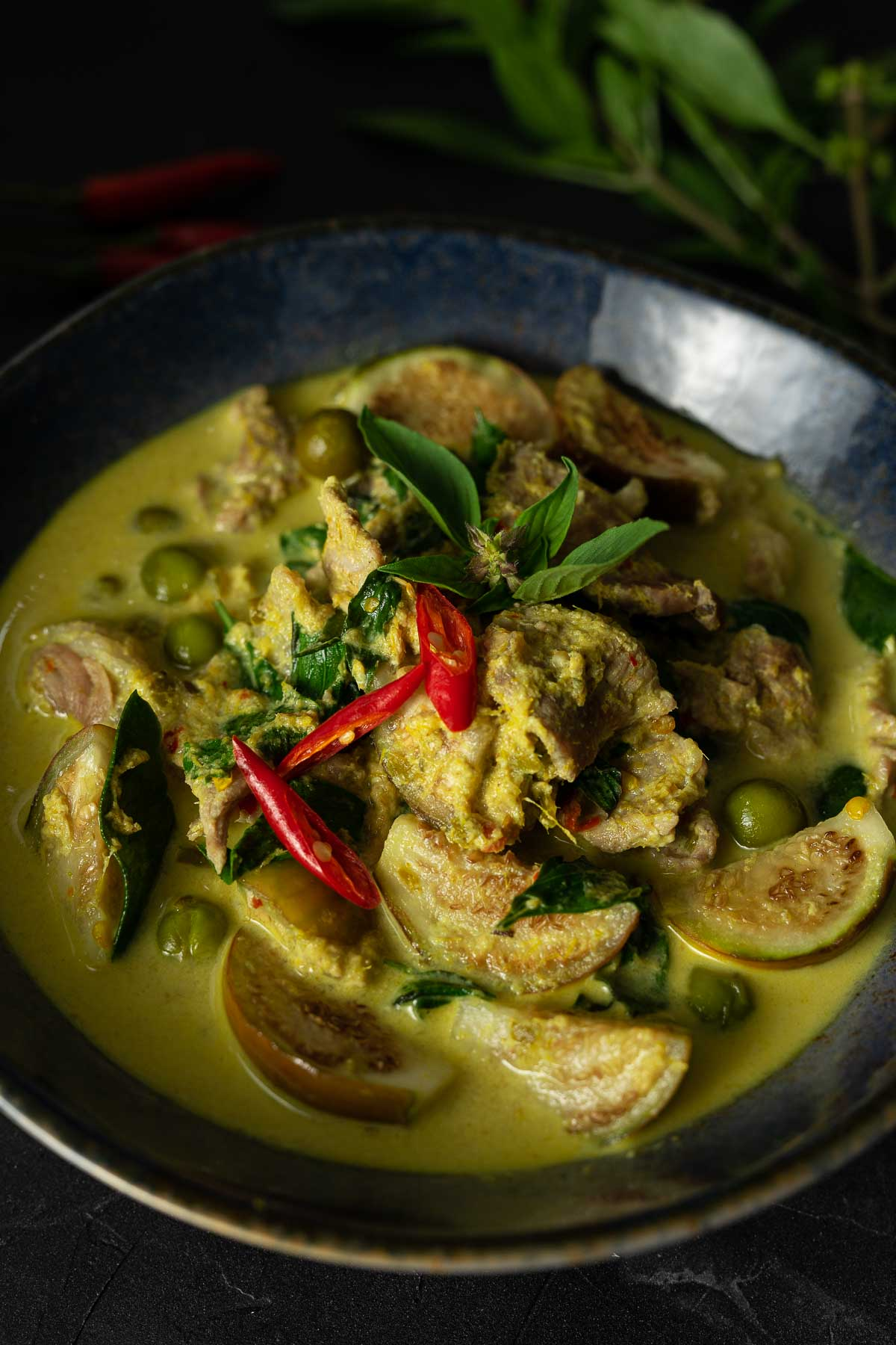 Thai green beef curry with eggplant garnished with Thai basil leaves and sliced red chilies in a blue bowl on a black surface