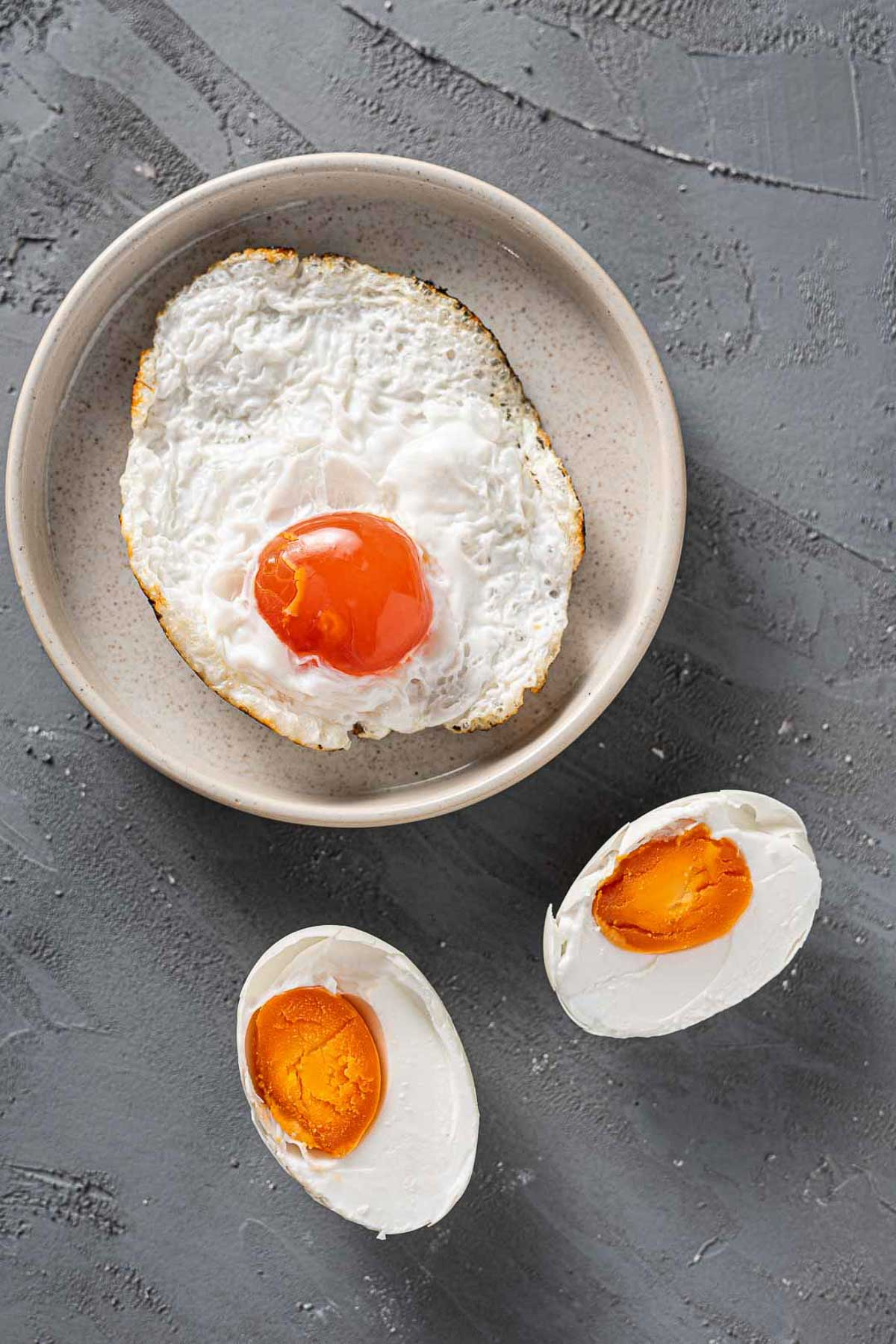 fried and boiled salted eggs on a gray surface