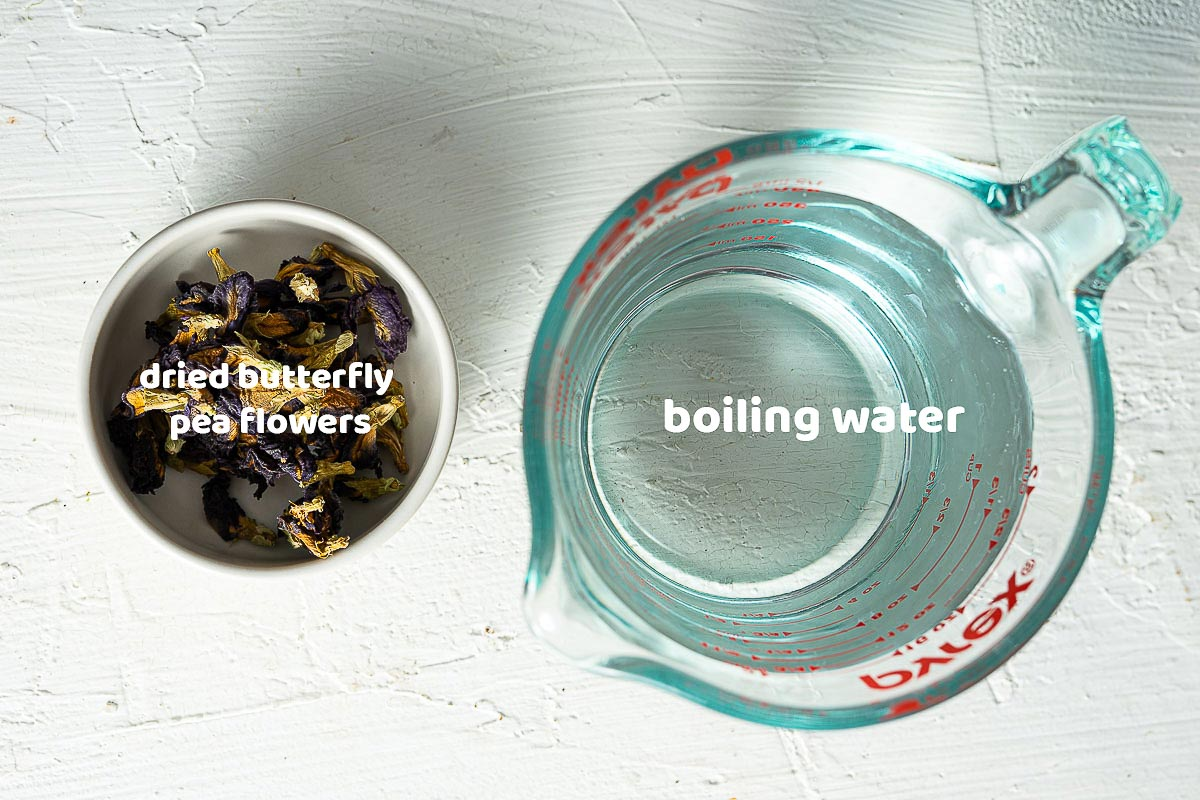 dried butterfly pea flowers in a white bowl and boiling water in a cup