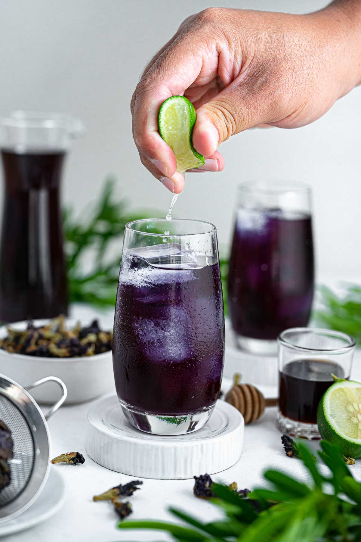 lime being squeezed into a glass of iced butterfly pea tea