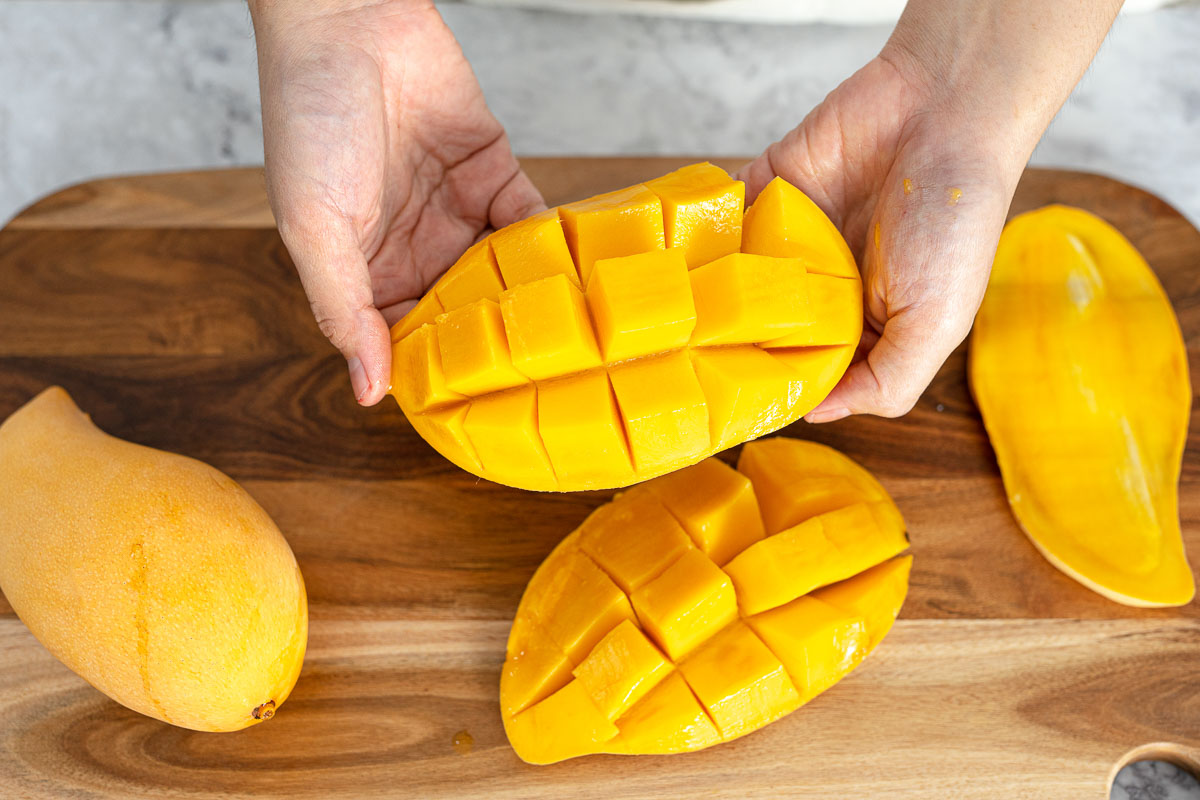 a Thai mango having been prepared in cubes for mango sticky rice