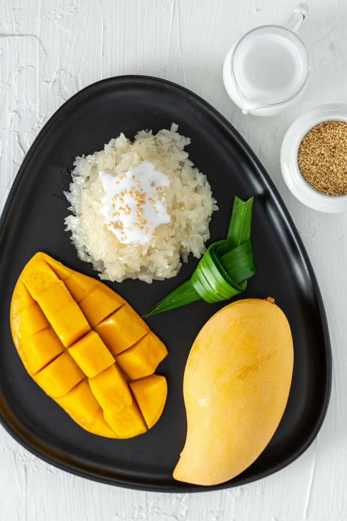 Thai mango sticky rice dessert with pandan leaves on a black plate